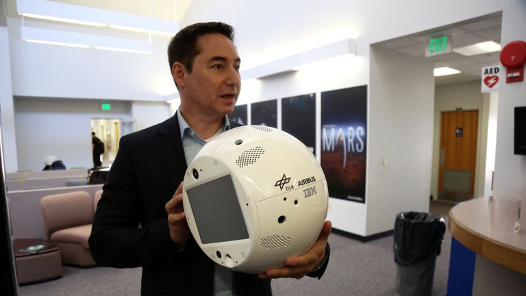 Airbus engineer Philipp Schulien holds a clone of an artificial intelligence bot named CIMON at the NASA News Annex in Florida