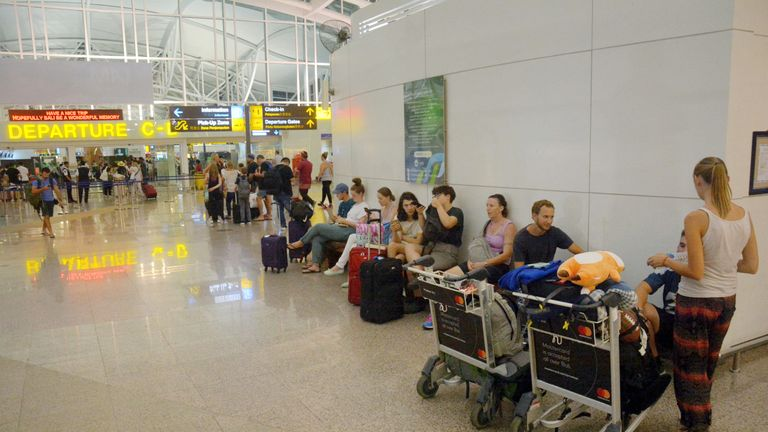 Passengers are seen waiting for flights outside the International Terminal at Ngurah Rai Airport after...