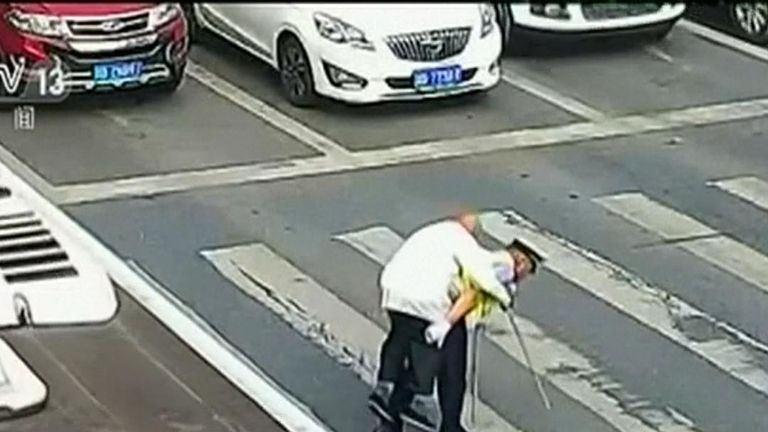 Elderly man is helped across busy China road in unusual way