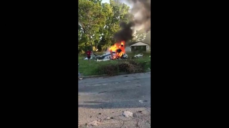 A teenager is seen emerging from a burning light aircraft near Detroit
