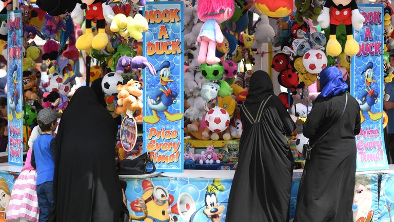 People play fairground games after morning prayers