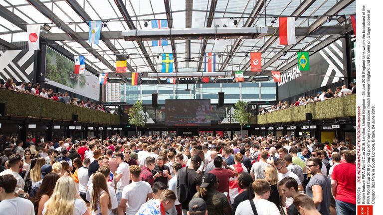 England fans watch the previous England and Panama game on a large screen at Croydon Box Park in South London
