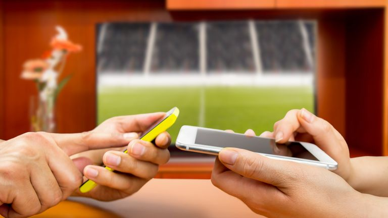 Friends using mobile phone and betting during a football match