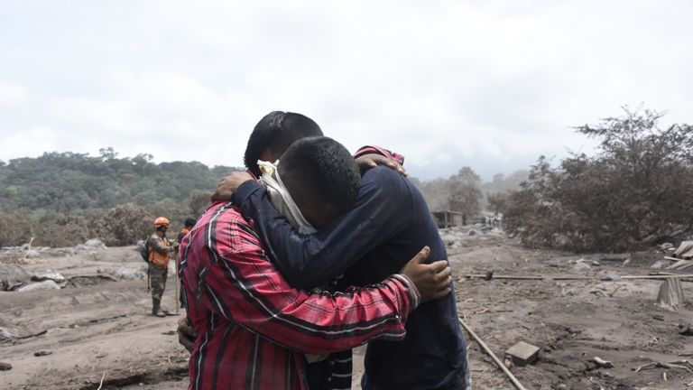 Guatemala volcano: Bryan Rivera, 22 (right), is comforted as he cries while searching for relatives, victims of the Fuego Volcano eruption in the ash-covered village of San Miguel Los Lotes, in Escuintla department