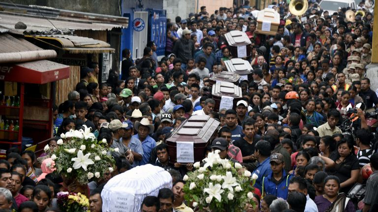 Residents carry the coffins of seven people who died following the eruption