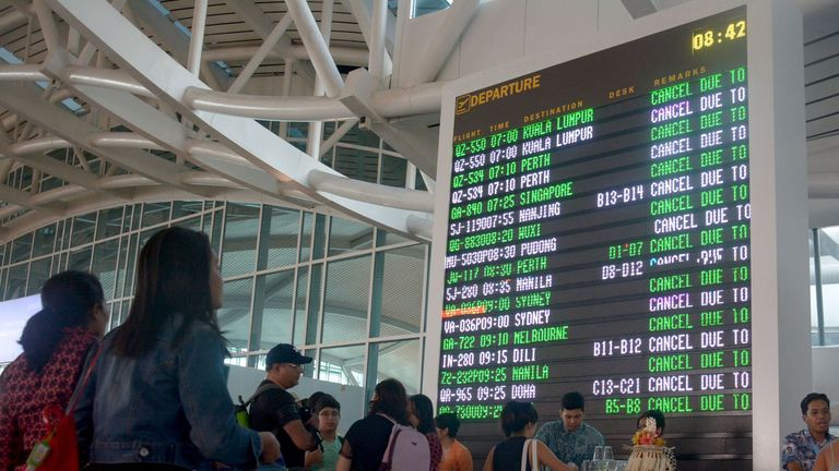 Travellers check their flights at Ngurah Rai airport in Denpasar, Bali which is closed on June 29, 2018 after a pilot report detected volcanic ash as high as 23,000 feet following Mount Agung's eruption. - Bali closed its international airport following a volcanic eruption on the Indonesian resort island that sent thick smoke and ash billowing 2,000 metres (6,500 feet) into the air, an official said. (Photo by GEDE ARDIASA / AFP) (Photo credit should read GEDE ARDIASA/AFP/Getty Images)