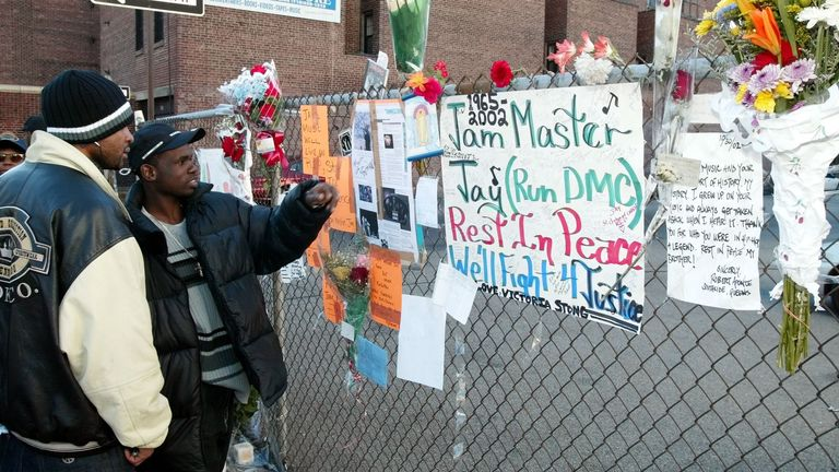 Olel Right (L) and Lionel Frazer (R) look at a wall of flowers and cards outside a music studio in Queens, New York 31 October, 2002 where former Run DMC member Jason Mizell, who was also known as DJ Jam Master Jay, was shot and killed late 30 October. There was no immediate word on the motive for the shooting of Jam Master Jay who was in his studio in New York's Queens neighborhood with another man. The other unidentified man suffers from a wound in the arm. AFP PHOTO/Mat