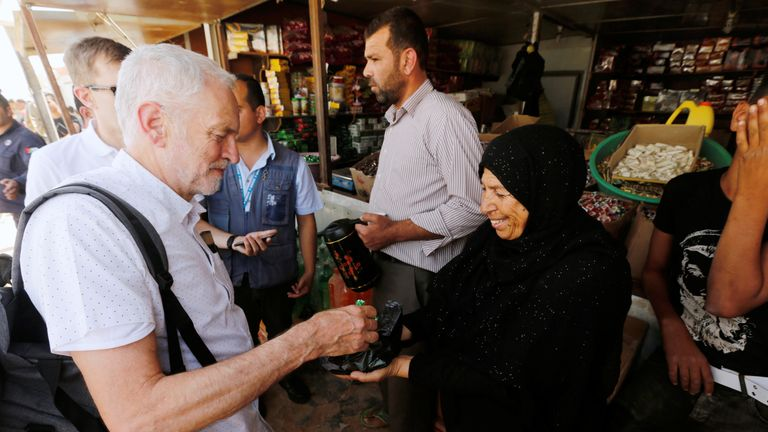 A Syrian refugee woman offers sweets to Britain's opposition leader Jeremy Corbyn during his visit to Al Zaatari refugee camp, in the Jordanian city of Mafraq, near the border with Syria, June 22, 2018. REUTERS/Muhammad Hamed