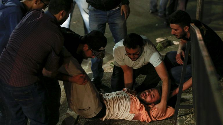 Jordanian protesters and security personnel tend to an unconscious man