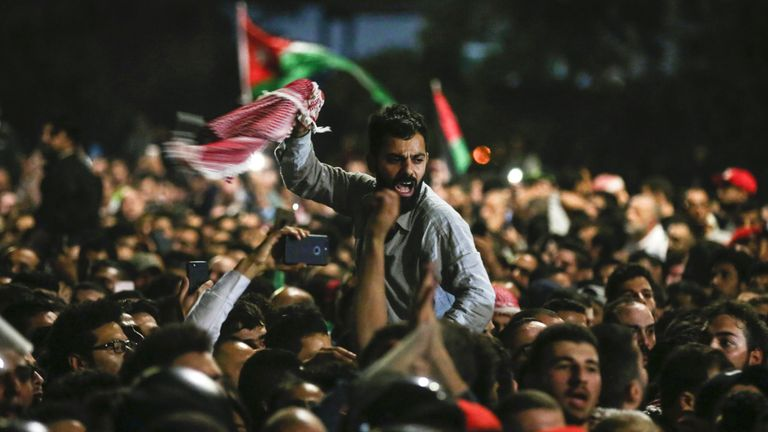 Jordanian protesters shout slogans and raise a national flag during a demonstration