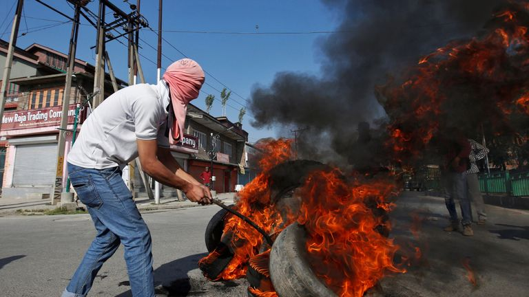 A masked protester burns tires during the funeral of Kaisar Ahmad Bhat in Srinagar