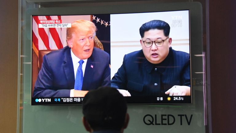 A man watches a television news screen showing US President Donald Trump (L) and North Korean leader Kim Jong Un (R), at a railway station in Seoul on May 25, 2018