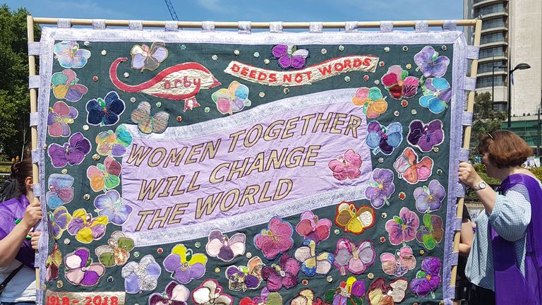 Women hold a banner reading 'Women together will change the world' in London