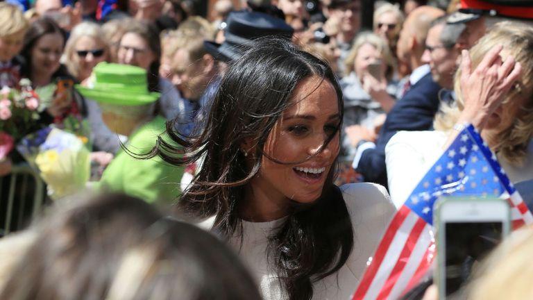 Meghan speaks as someone waves an American flag