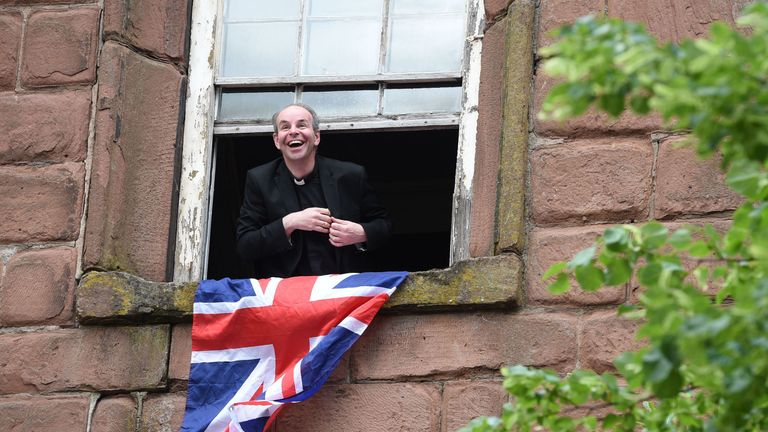 A priest looks out of a window for the arrival of Meghan and the Queen