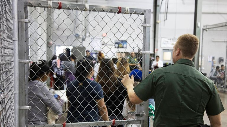 A Border Patrol agent watches detainees