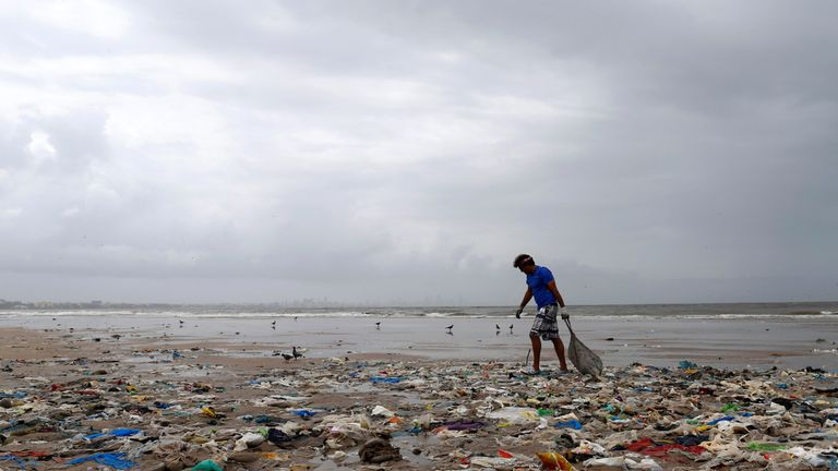 A volunteer collects rubbish from a beach in Mumbai