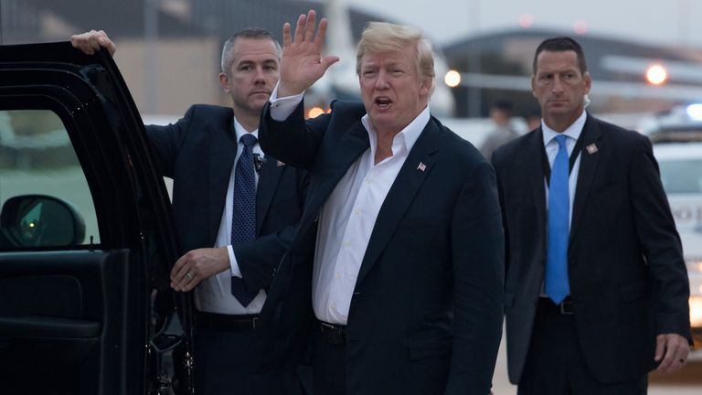 Donald Trump waves as he steps off Air Force One on his return to the US