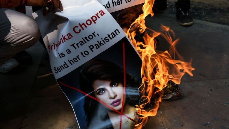 A burning poster describing Chopra as a traitor