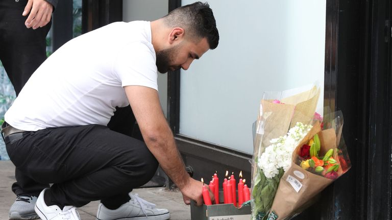 A man lights candles next to flowers left after Rashan Charles' death