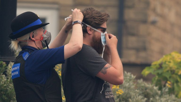 A PCSO helps a member of the public put on a face mask