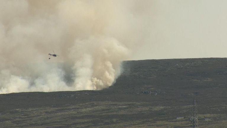 A helicopter drops water onto the fire on Saddleworth Moor