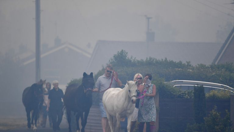 Residents move their horses as the fire continues to rage on Saddleworth Moor