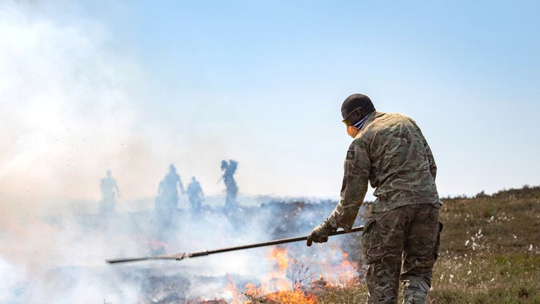 Soldiers from The Highlanders, 4th Battalion, Royal Regiment of Scotland work to bring the fire under control on Saddleworth Moor