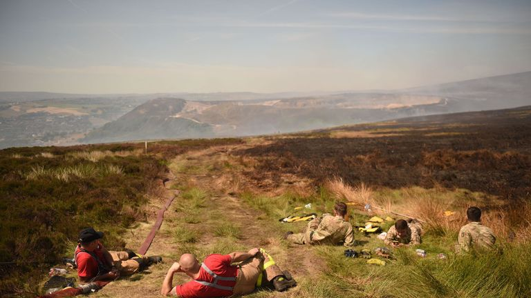 Firefighters and soldiers take a break from fighting a wildfire on Saddleworth moor near Stalybridge, northwest England on June 28, 2018
