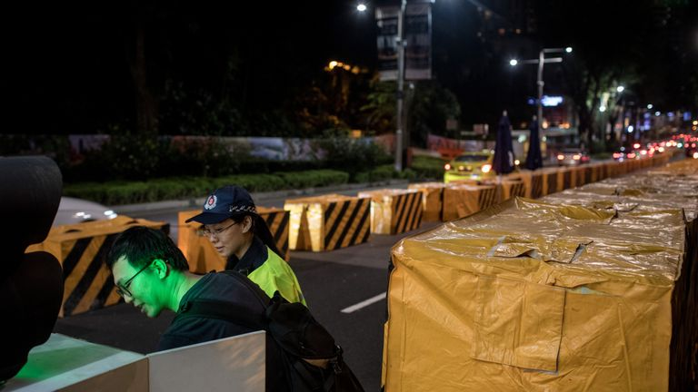 A man sets up an electronic security gate at a vehicle checkpoint in front of the St. Regis Hotel on June 9, 2018