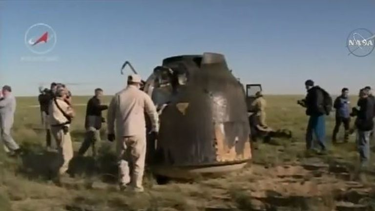 The capsule is seen on the grassland where it landed
