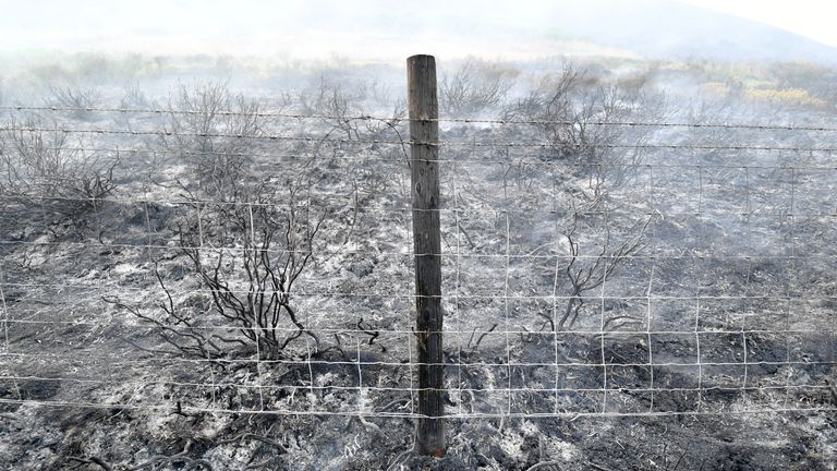 A scorched fencepost where a large wildfire has burnt the the moors above Stalybridge