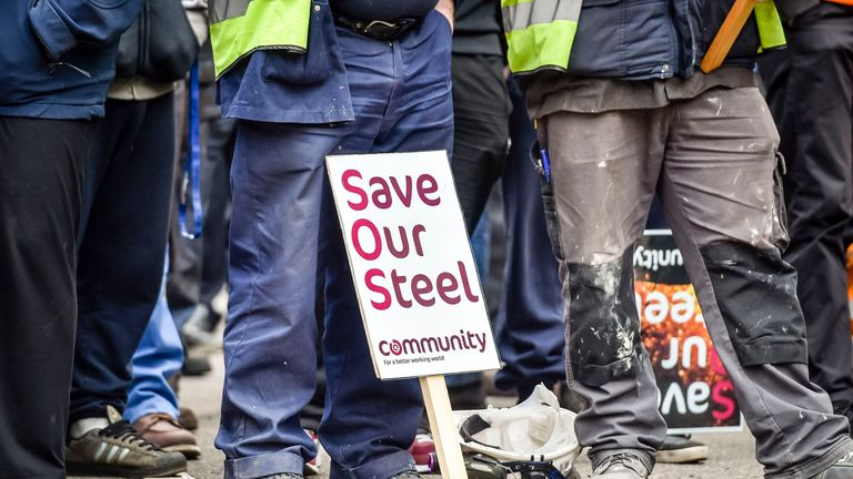 A placards is rested by steelworkers feet as they wait to meet Secretary of State for Business