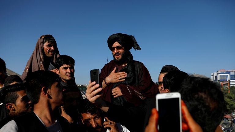People take selfies with a Taliban fighter in Kabul