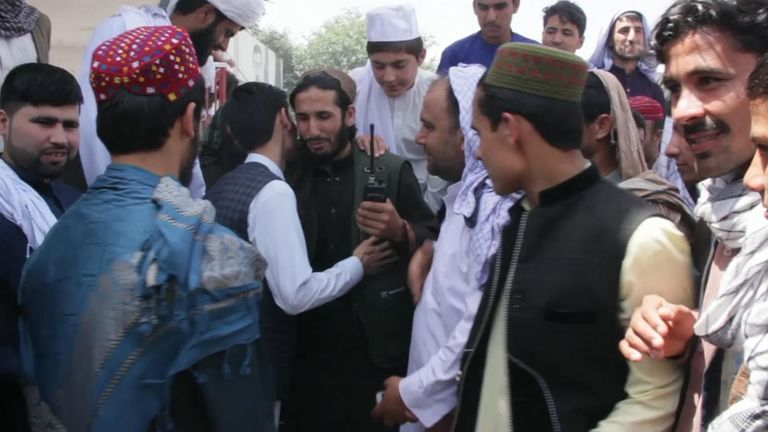 A Taliban leader is kissed by locals in Kunduz during the ceasefire
