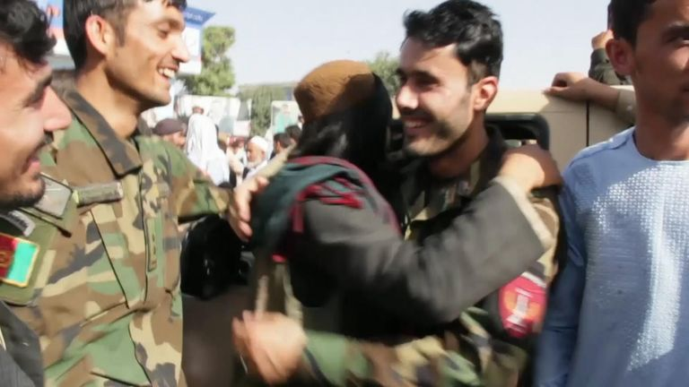 An Afghan security official hugs a Taliban fighter