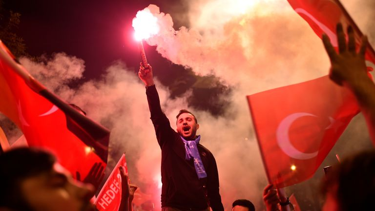 People let off flares outside the AKP party's headquarters in Istanbul