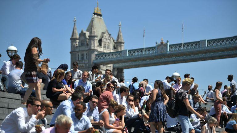 People enjoy their lunch break in the sunshine near Tower Bridge in London