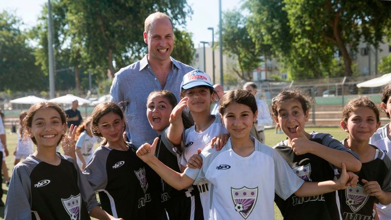 Prince William poses with the Jewish and Arab children he played football with in Jaffa