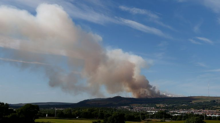 Smoke rises from a grass fire on Winter Hill near Bolton
