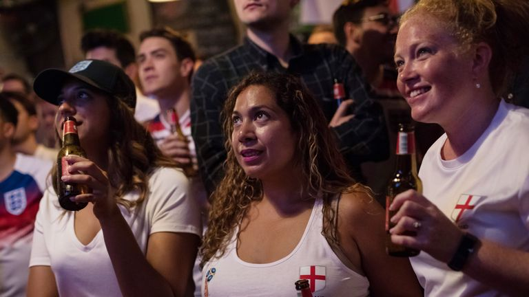 Supporters watch England's national team first Football World Cup match against Tunisia at a bar in London