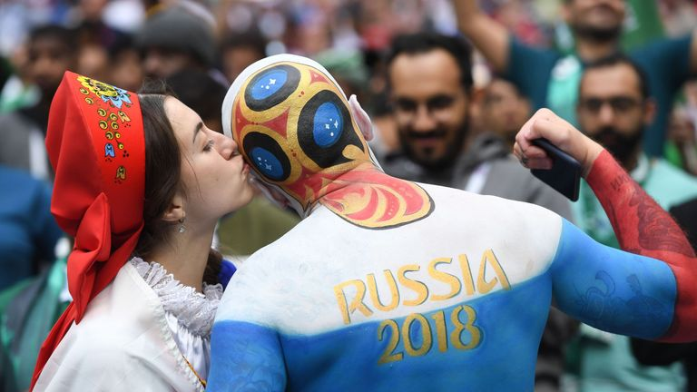 A Russia fan kisses another supporter before the start of the Russia 2018 World Cup Group A football match between Russia and Saudi Arabia at the Luzhniki Stadium in Moscow on June 14, 2018