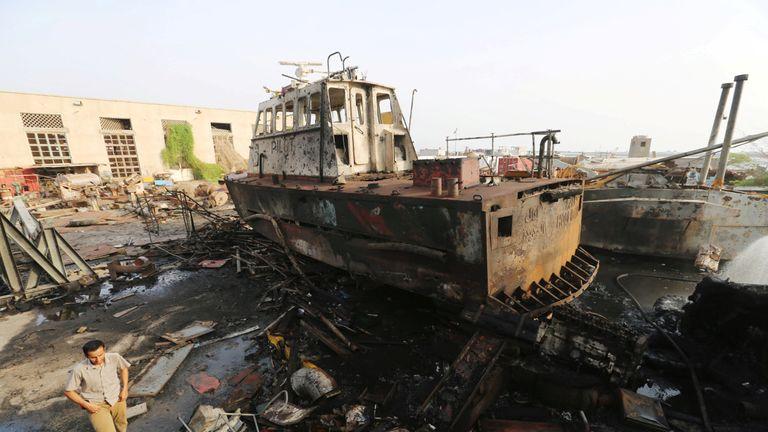 A worker walks past a tug damaged by an air strike on the maintenance hub at the Hodeida port, Yemen