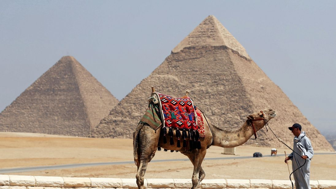 A man waits for tourists to rent his camel in front of the Great Giza pyramids on the outskirts of Cairo, Egypt, August 31, 2016. Picture taken August 31, 2016