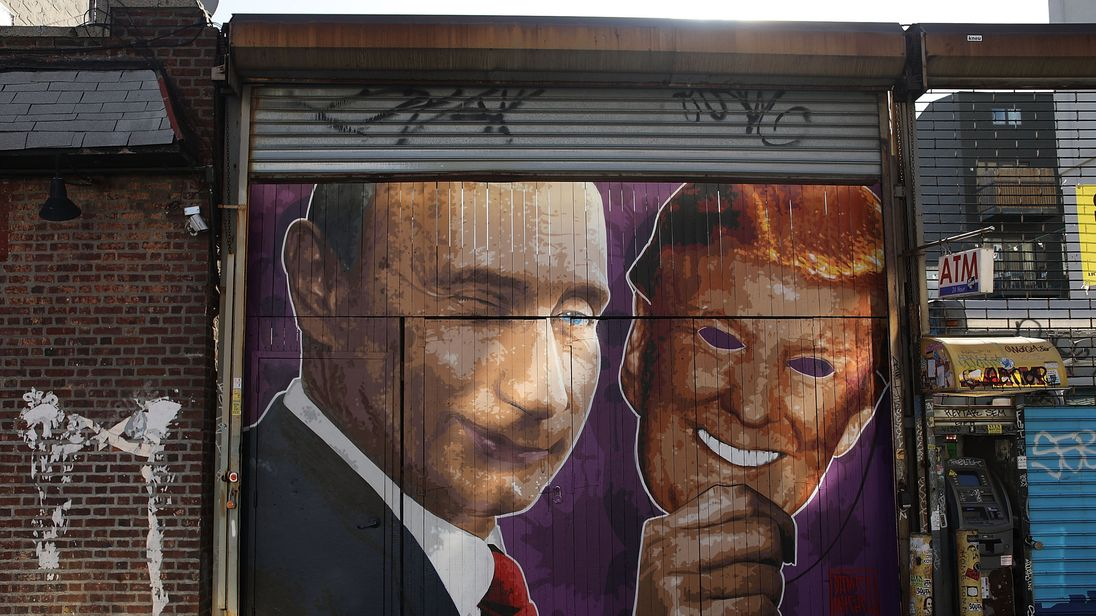 Mural depicting a winking Vladimir Putin taking off his Donald Trump mask on a storefront in Brooklyn New York