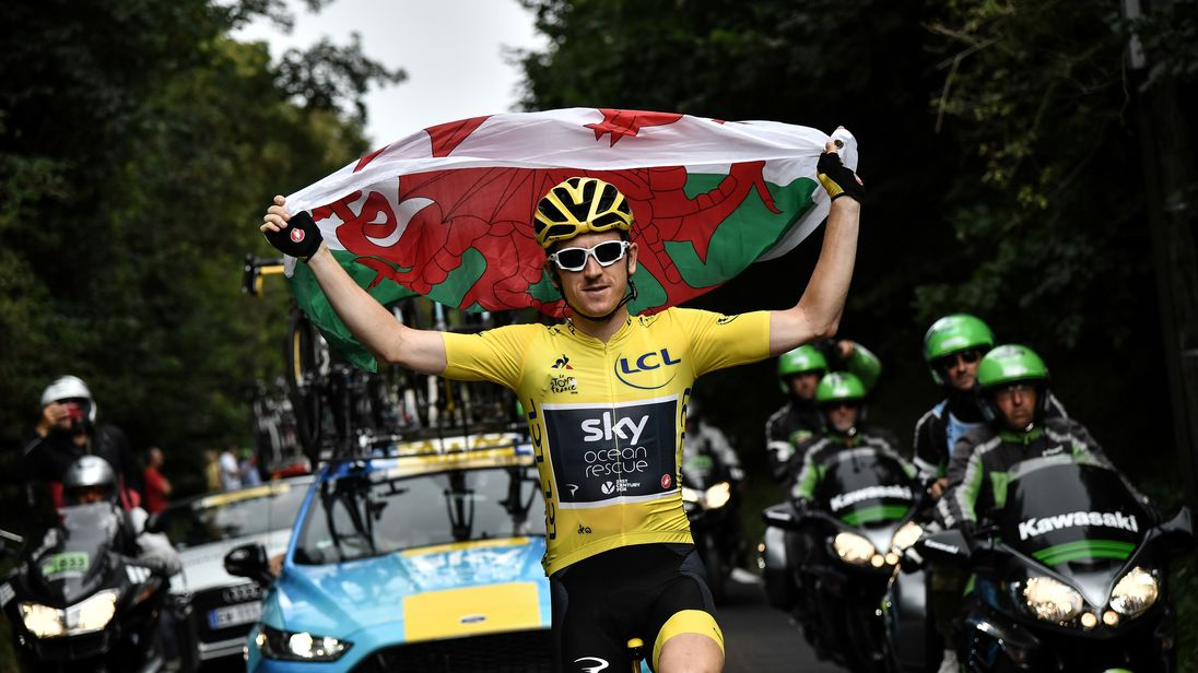 Great Britain's Geraint Thomas holds the Welsh flag