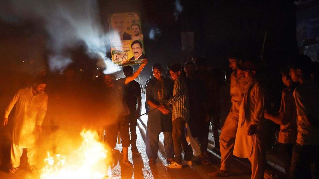 Supporters of former Pakistani Prime Minister Nawaz Sharif burn tyres during a protest ahead of of the arrival of Nawaz from London