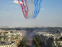 The Patrouille de France jets perform As supporters welcome France players for victory parade after they Russia 2018 World Cup final win