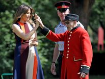 Melania Trump high-fives with Chelsea Pensioner during a game of bowls at The Royal Hospital Chelsea in central London