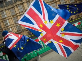 Anti-Brexit demonstrators protest with flags outside the Houses of Common on February 26, 2018 in London, England